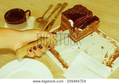 Female cutting chocolate cake on wooden table. Tasty cake and coffee - Retro color
