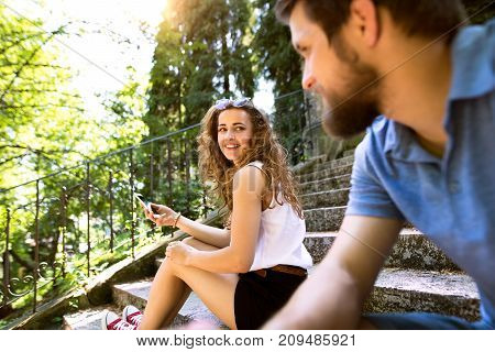 Beautiful young couple with smart phone sitting on stairs in old town, watching or reading something. Sunny spring day.