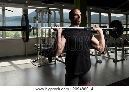 Athlete In The Gym Exercising Shoulder With Barbell
