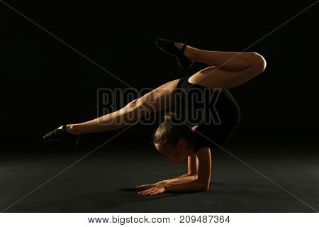 Young girl gymnast on the black background