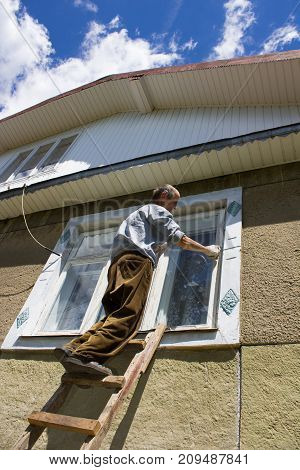 the man brushes the window with a spindle paint