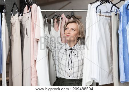 Woman Choosing Blouses At Store