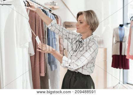 Woman Looking At Tag Of Shirt