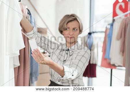 Woman Looking At Tag On Shirt