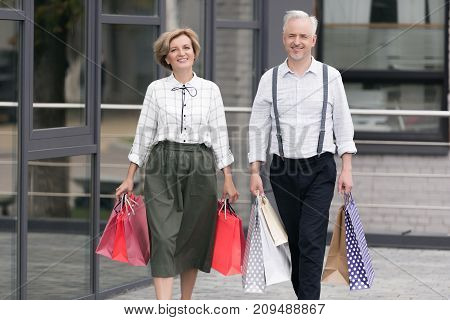 Husband And Wife Walking With Shopping Bags