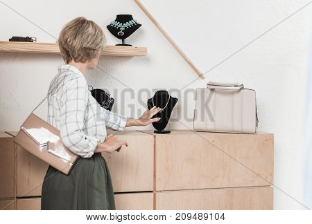Woman Looking At Necklace At Store