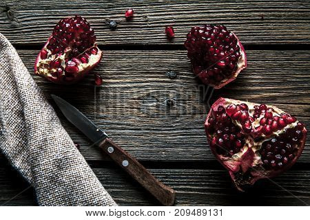 Ripe pomegranates, napkin and table knife on white wooden background