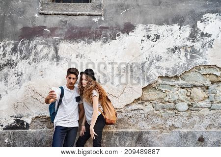 Two beautiful young tourists with smartphone and camera in the old town, taking selfie with the smartphone.