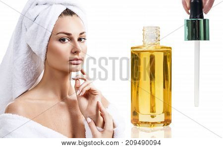 Cosmetic oil applying on young woman face with pipette. Beauty therapy concept.