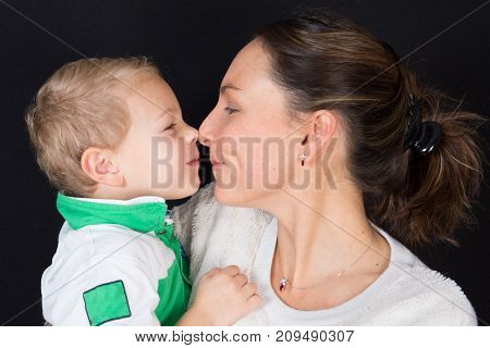 Beautiful Woman And Her Cute Little Son Are Touching Their Noses And Smiling On Black Background