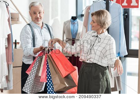Wife Giving Shopping Bags To Husband