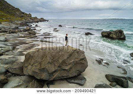 Young traveler standing on the top of a large rock to enjoy the view at Uttakleiv beach on Lofoten islands in Norway.