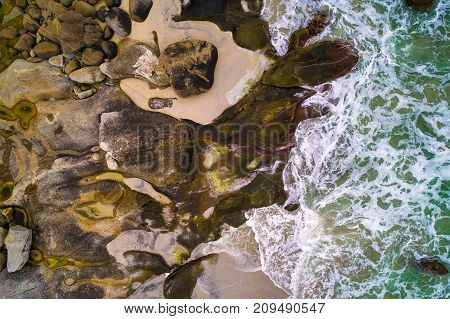 Aerial view looking down at sea waves hitting rocks of a beach on Lofoten islands in Norway.