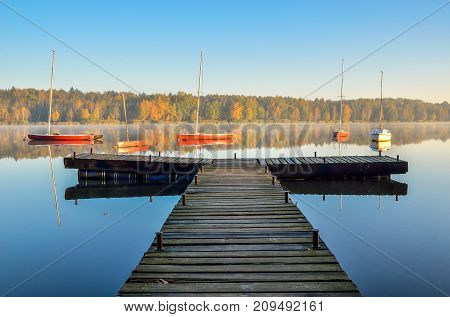 Beautiful autumn landscape. Wooden pier and boat on the lake.