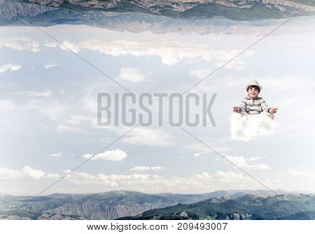 Young boy keeping eyes closed and looking concentrated while meditating on cloud in the air between two nature worlds.