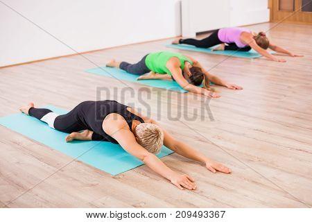 Three girls practicing yoga, Shashankasana / Hare pose