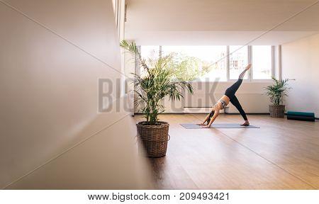 Fitness woman practising yoga indoors. Female doing forward bend stretching yoga exercise. Three legged dog pose.