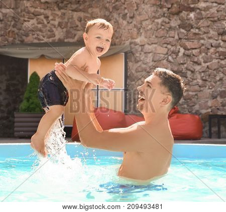 Child swimming lesson. Cute little boy learning to swim with father in pool