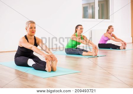 Three girls practicing yoga, Paschimottanasana / Seated Forward Bend pose