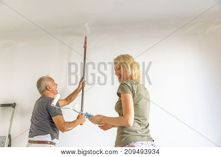 Smiling caucasian woman with senior painter man at work heaving fun whitewashing a white wall with paint roller in empty room for renovation.