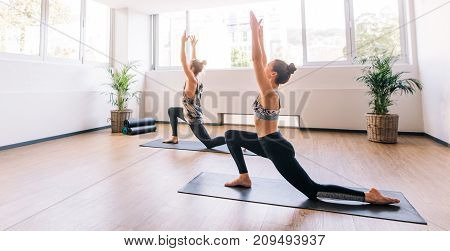 Two young people working out indoors. Fitness class doing yoga. Man and woman stretching forward in warrior pose.