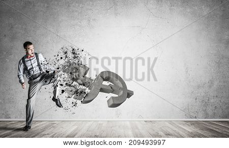 Young furious businessman in empty room crash with leg kick stone dollar symbol