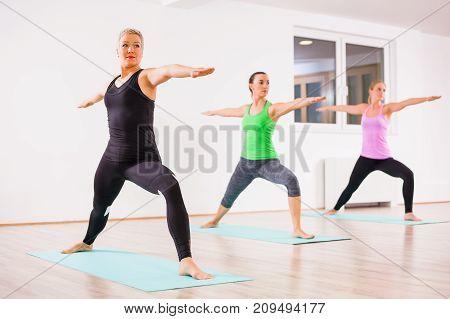 Three girls practicing yoga, Virabhadrasana / Warrior 2 pose