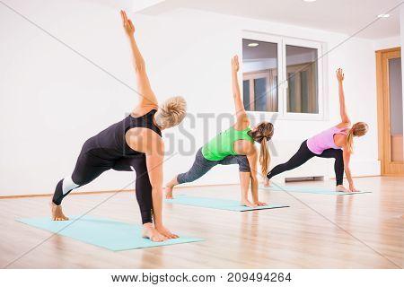 Three girls practicing yoga, Trikonasana / Bikram triangle right pose