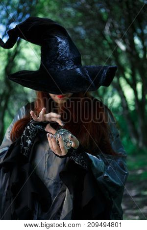Portrait of witch in long black hat