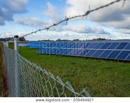 Solar panel or photovoltaic farm behind metal fence on green field with dramatic cloudy sky in North Germany.
