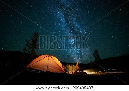 Man tourist near his camp tent at night under a sky full of stars. Orange illuminated tent.