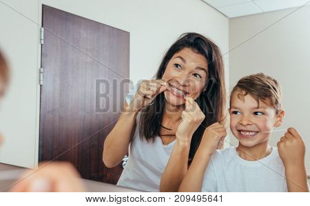 Little boy with his mother in bathroom cleaning teeth with dental floss. Woman with son looking in mirror and cleaning teeth.