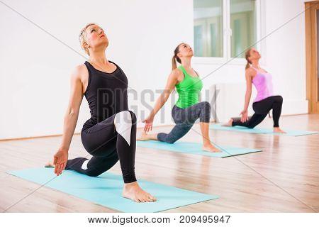 Three girls practicing yoga, Virabhadrasana / Warrior pose