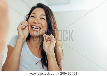 Woman looking in the bathroom mirror and using dental floss to clean her teeth. Reflection of woman in bathroom mirror while brushing teeth in morning.