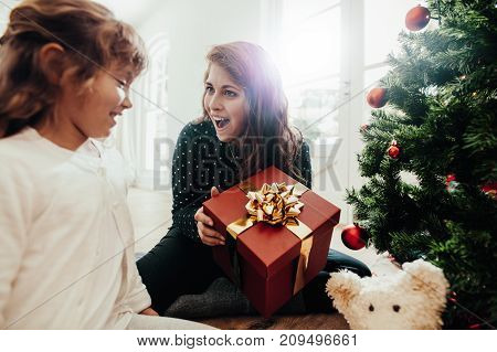 Family celebrating Christmas with gifts and Christmas tree at home. Excited mother holding gift box looking at her daughter sitting near Christmas tree.