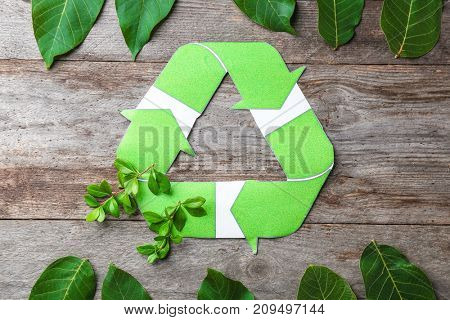 Composition with symbol of recycling and leaves on wooden background