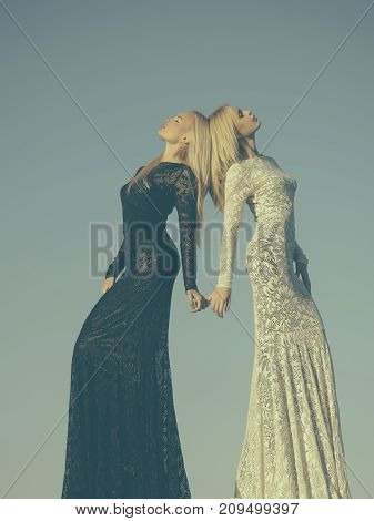 Two Girls With Long Blond Hair Posing On Grey Sky