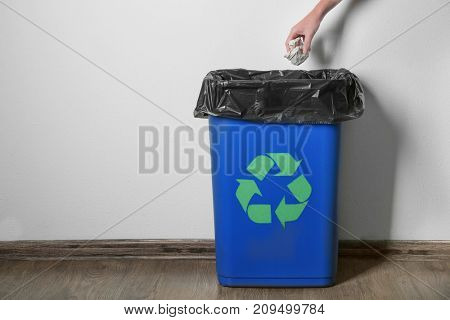 Woman throwing garbage in rubbish bin with logo of recycling in room