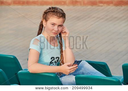 The girl on the seat in the stands.Girl loves to listen to the song in the phone.Closeup portrait of a sporty teen girl.