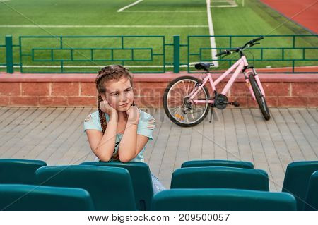 Sporty kid posing with a Bicycle. The girl in the blue seats of the stadium looks into the distance.The bike is set on blurred background. Place for text. series.