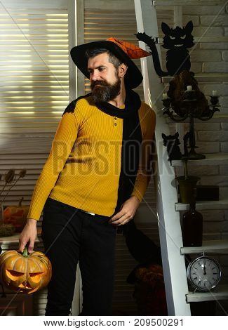 Magician And Carved Pumpkin. Man With Beard Holds Jack Lantern