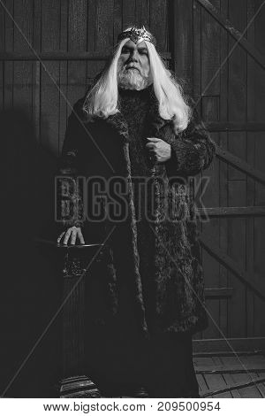 old druid bearded man with long beard on serious face and hair in fur coat and crown with gem stones jewellery on wooden background near column