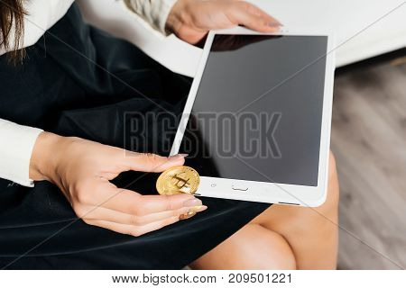 business lady holding a tablet and gold bitcoin, virtual cryptocurrency concept