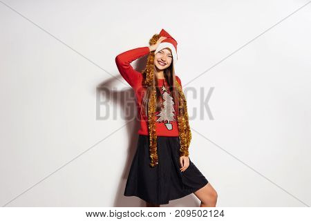 laughing girl in a New Year's cap and with a festive tinsel on the neck