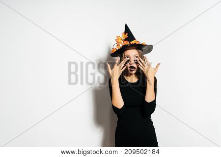Gothic young girl in witch's Halloween costume and black hat, adorned with yellow leaves, looks surprised