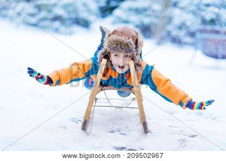 Little boy enjoying sleigh ride during snowfall. Child sledding on snow. Preschool kid riding a sledge. Child play outdoors. Kids sled in snowy winter park. Active fun for family Christmas vacation.