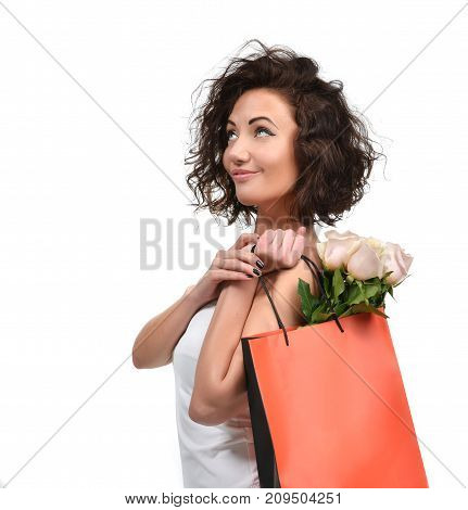 Pretty young brunette woman with shopping bag and pink roses flowers smiling looking at the corner isolated on a white background