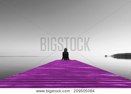 View from the back of beautiful and healthy girl sitting on pink wooden pier. Vacation resort and traveling concept. Black and white
