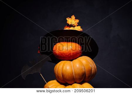 Halloween carved pumpkins in a black witch hat stand on top of each other