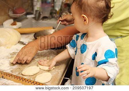 Woman Baking Pies In Kitchen With Little One-two Granddaughter. Grandma Cooks Pies And Learn Child.